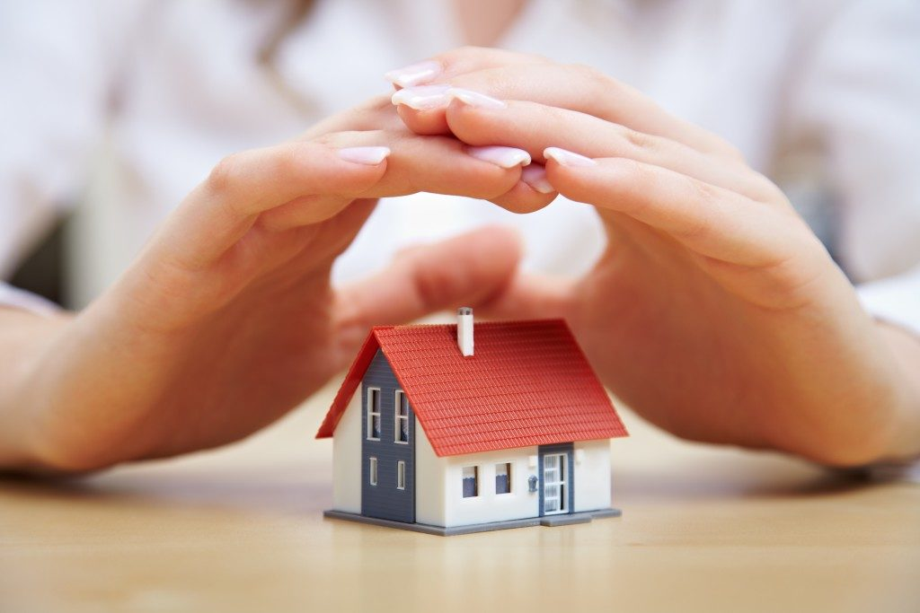 hands covering a miniature house