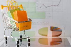 Colourful paper bags in yellow trolley on tablet with chart background