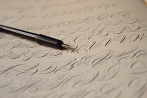pen on top of paper written with calligraphy